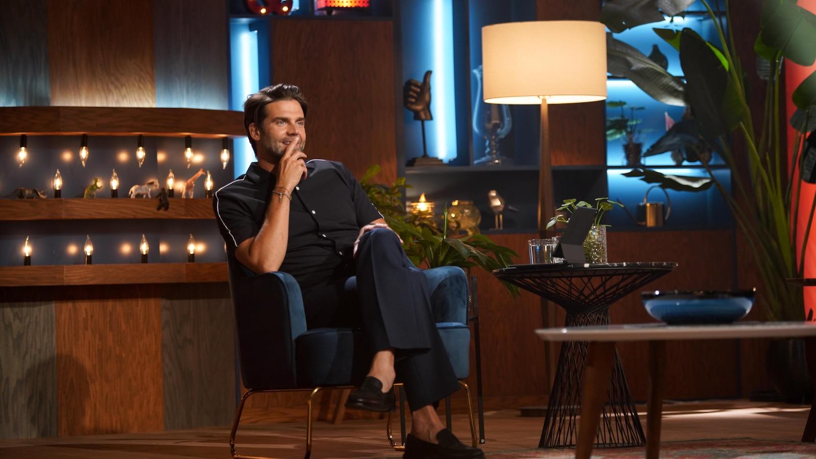 L'homme est assis dans un fauteuil avec des plantes à côté de lui et il sourit en regardant devant lui.