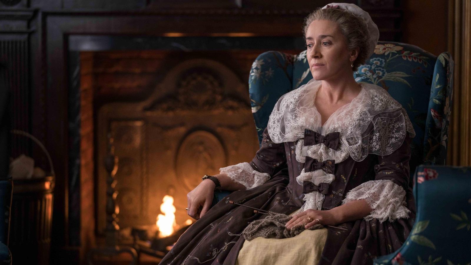 Une dame noblement vêtue est assise sur un fauteuil près d'une cheminée.