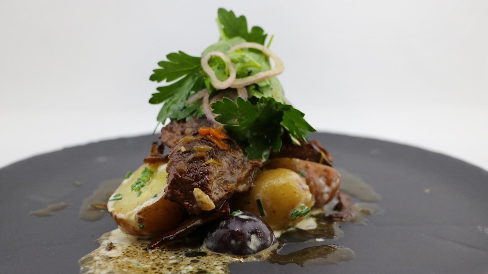 La viande est posée sur les pommes de terre. Des herbes fraîches sont posées sur la viande.