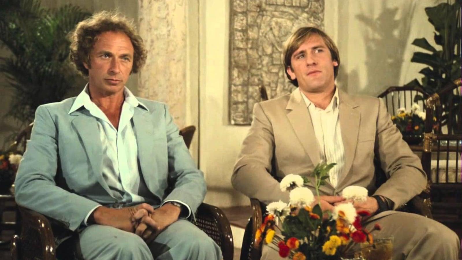 Un homme en costume bleu clair, un autre en costume sable, assis côte à côte.