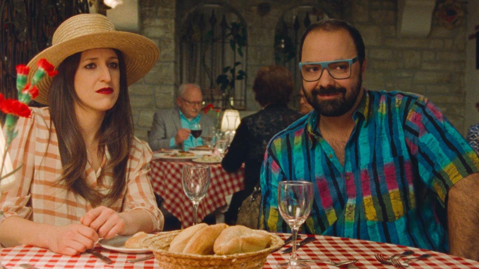 Une femme avec un chapeau (Anne-Élisabeth Bossé) et une homme portant une chemise colorée (Mani Soleymanlou) attablés à un restaurant.