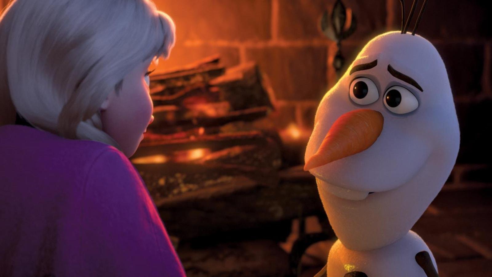 Un bonhomme de neige face à une jeune fille blonde.