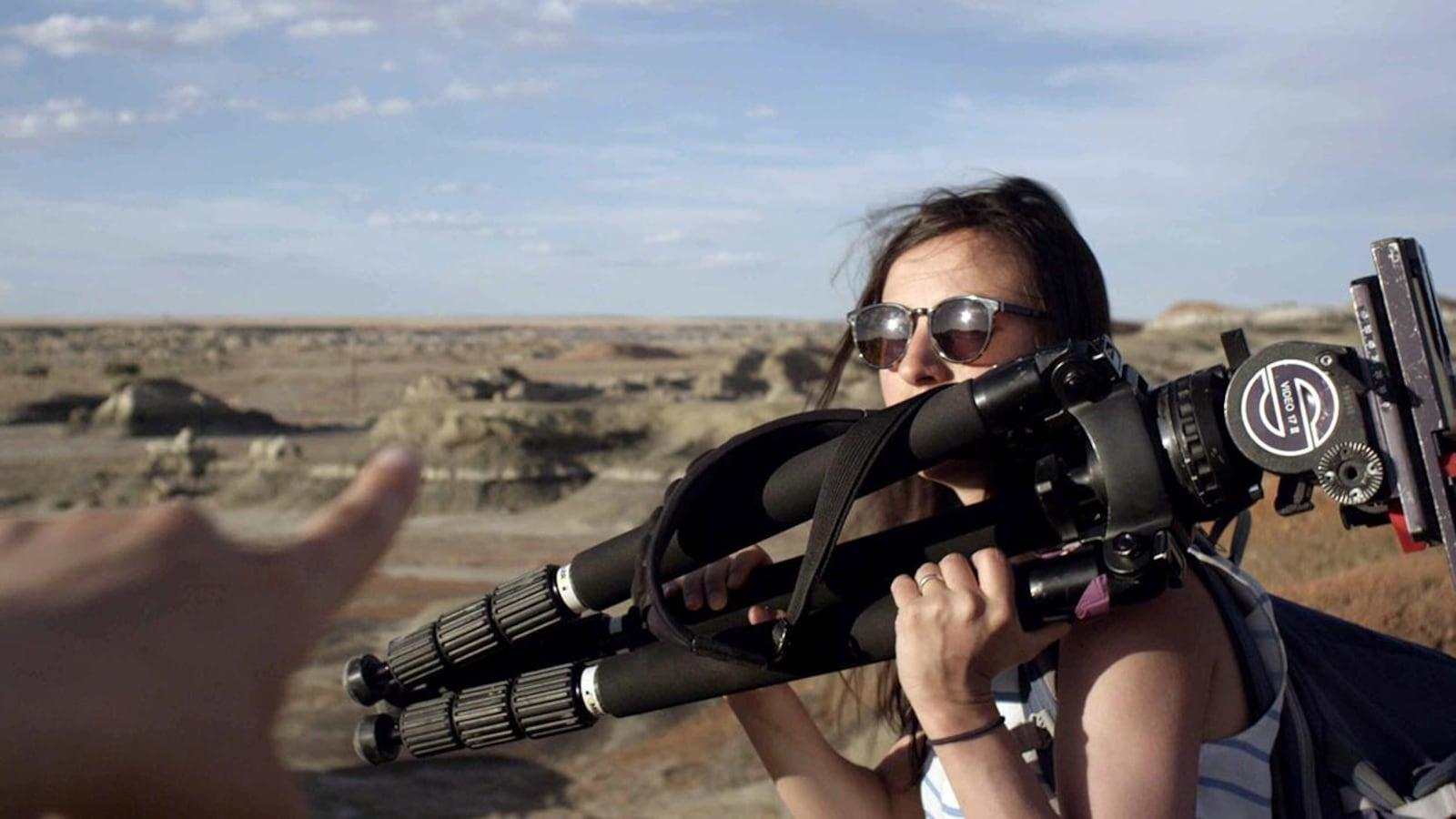 Une jeune fille, dans le désert, avec un trépied sur l'épaule.