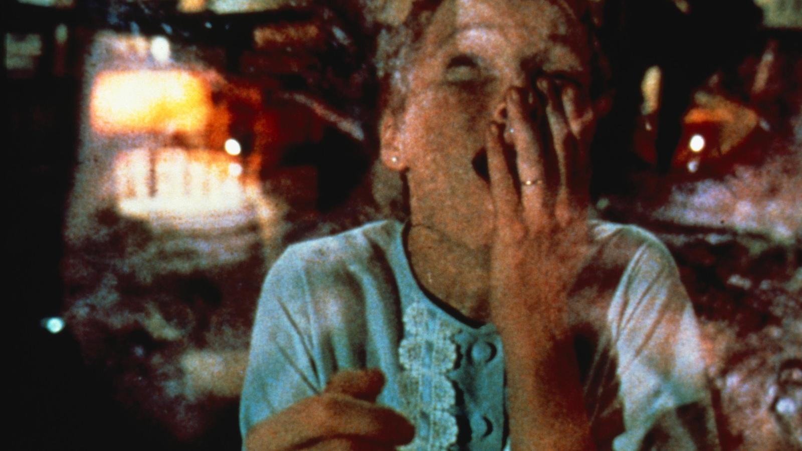 Une jeune femme la main sur la bouche, une image démoniaque en surimpression