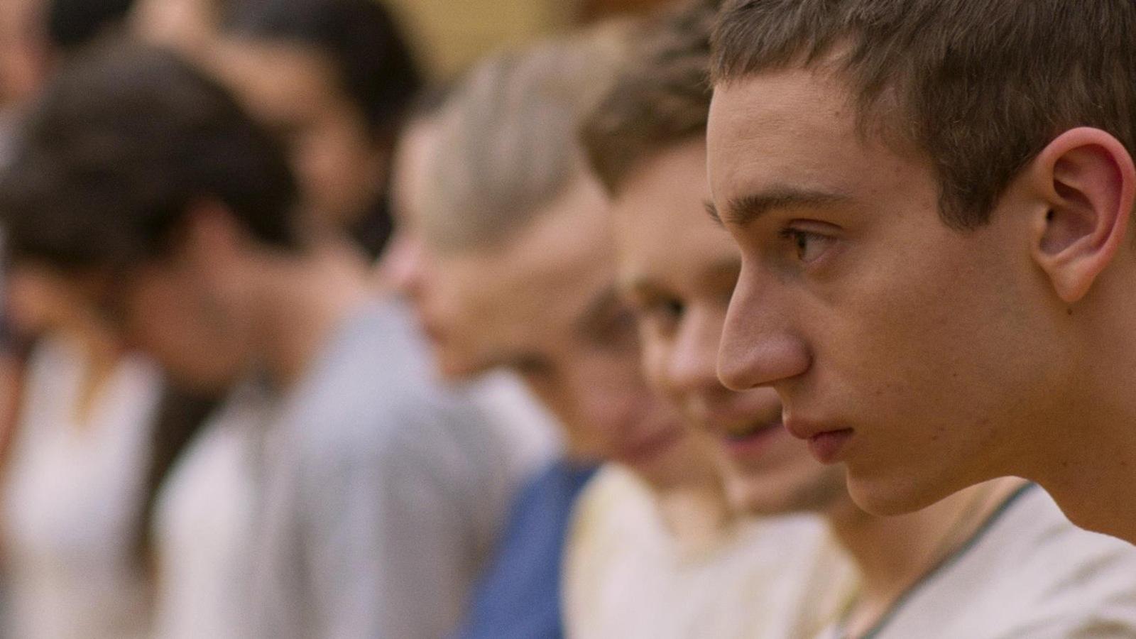Des jeunes hommes, de profil, sur une ligne de départ.