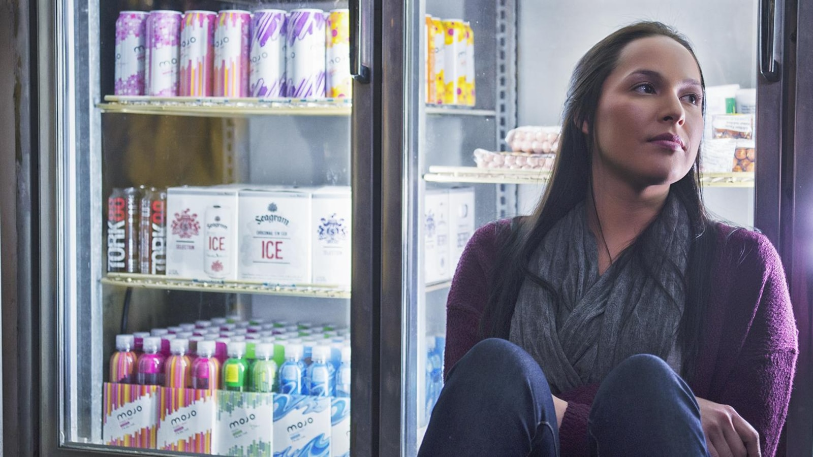Une jeune fille assise à terre devant un frigo de bières.