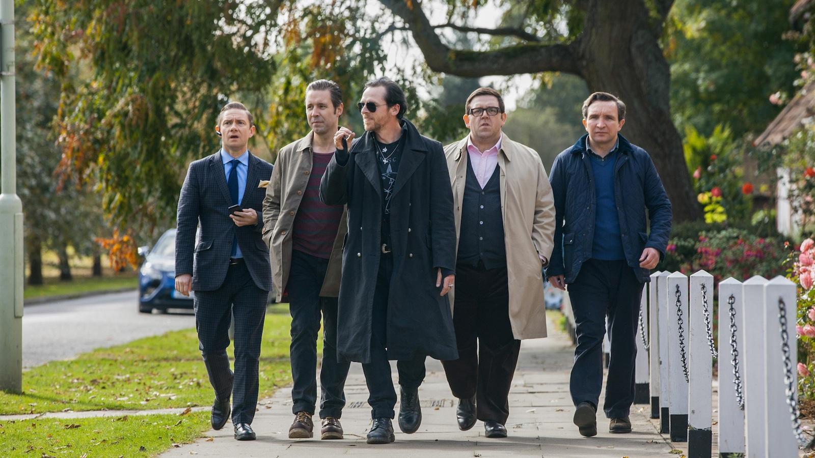 Un groupe d'hommes marche dans la rue.