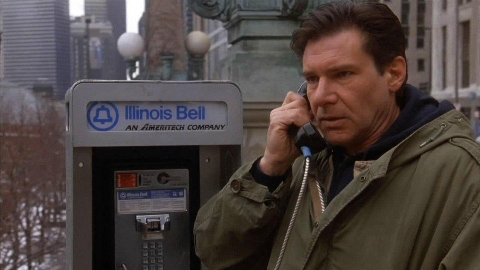 Un homme parle dans le combiné d'une cabine téléphonique.