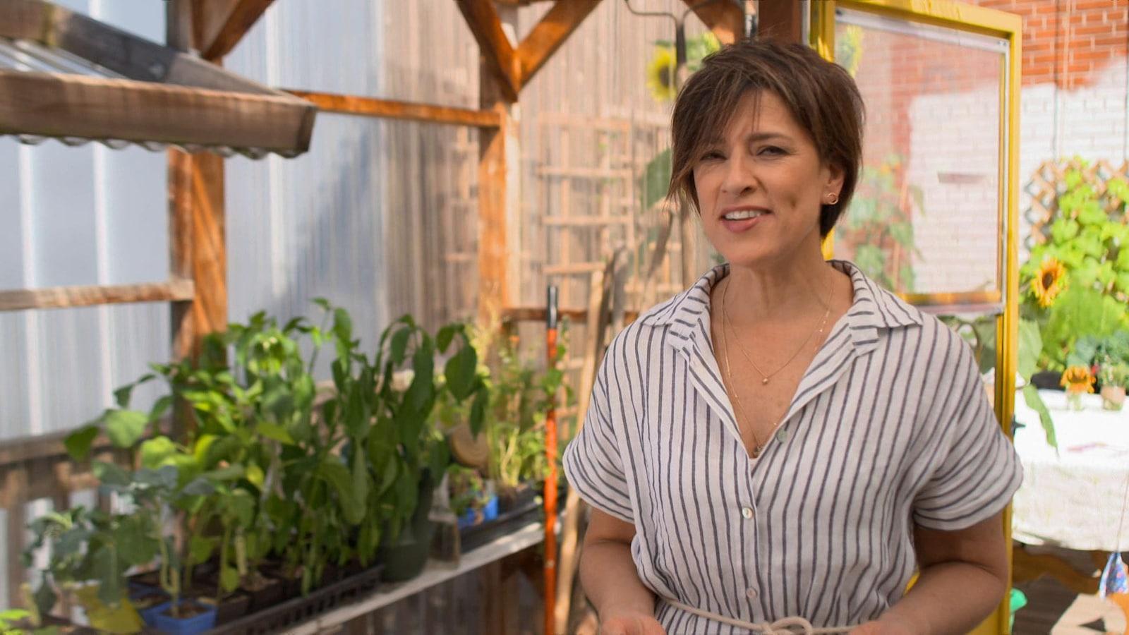Dans une serre où poussent des plants de légumes, Johanne Despins s'adresse à la caméra.