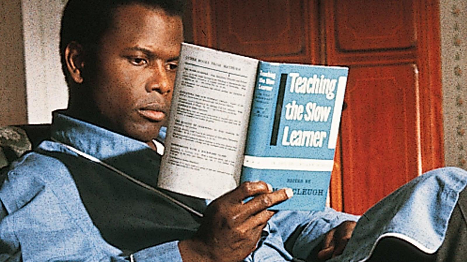 Un homme assis lit un livre.