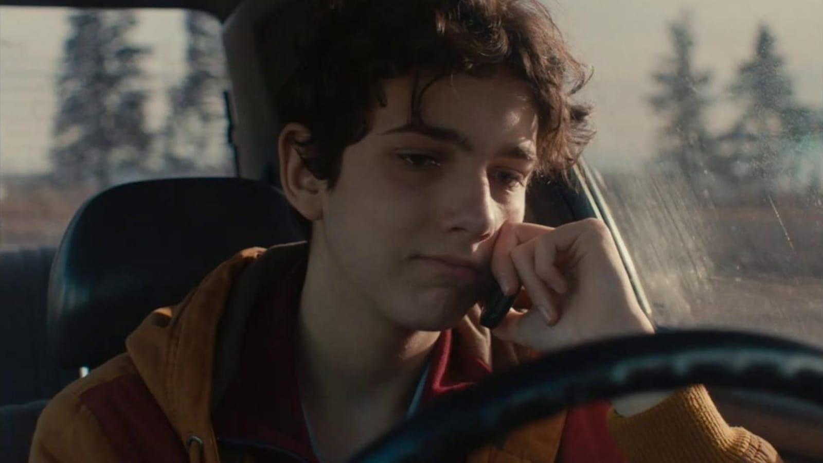 Un jeune homme (Justin Leyrolles-Bouchard) assis dans une voiture, au téléphone, les yeux humides.