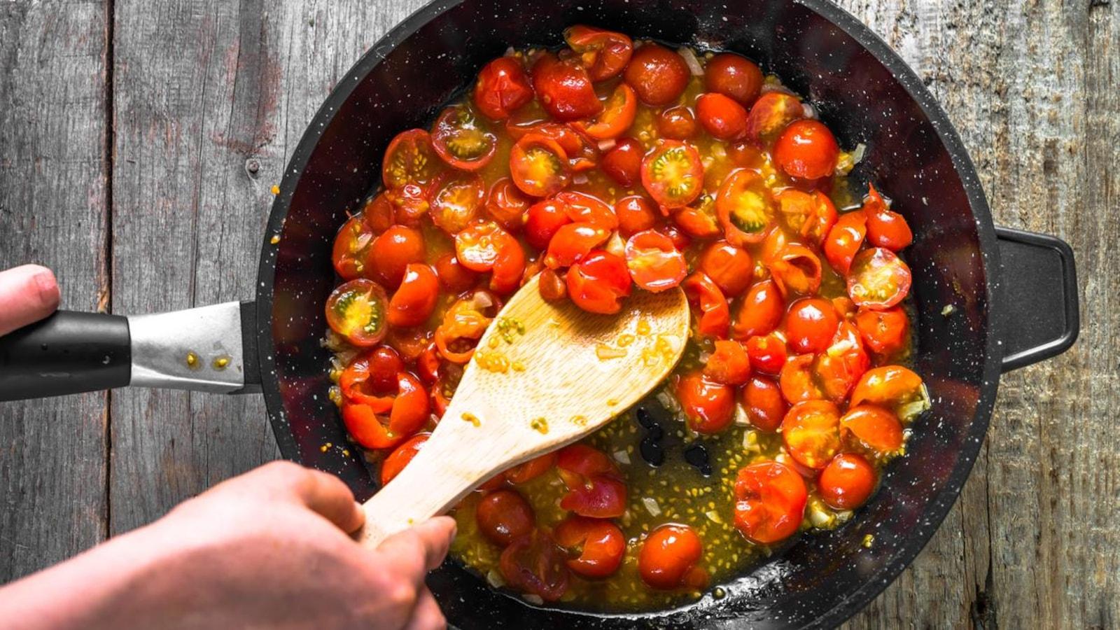 Une personne fait frire des tomates cerises dans une poêle.