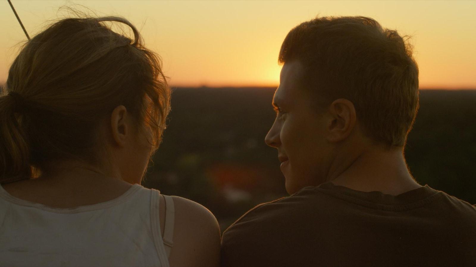Une jeune femme et un jeune homme de dos, devant le soleil couchant.