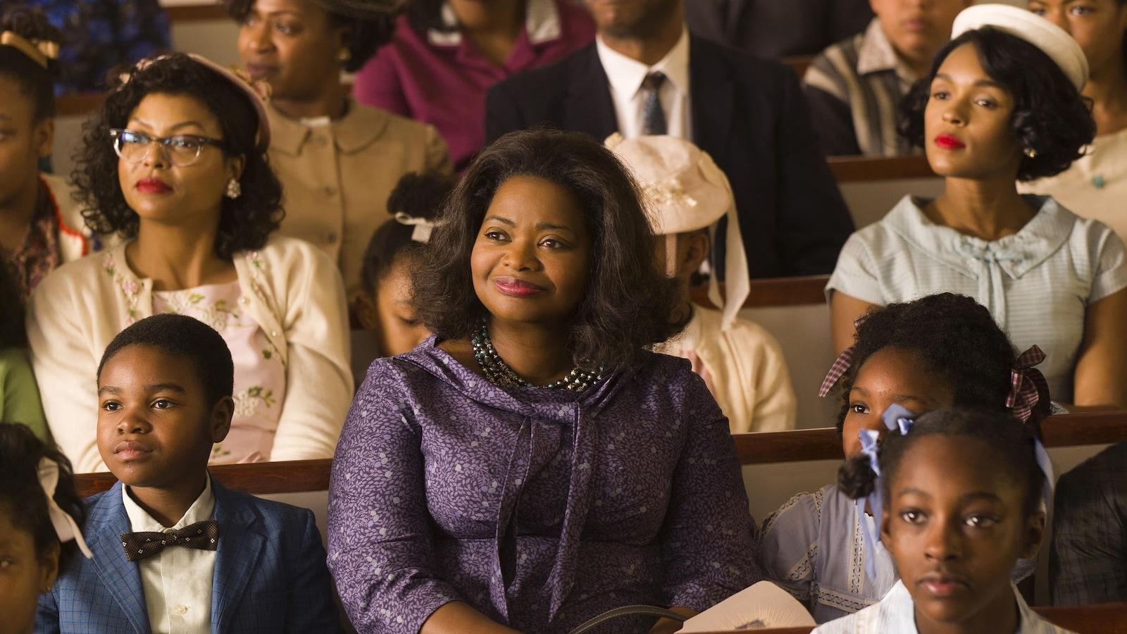 Une femme (Octavia Spencer) assise sur un banc d'église, entourée de femmes et d'enfants.
