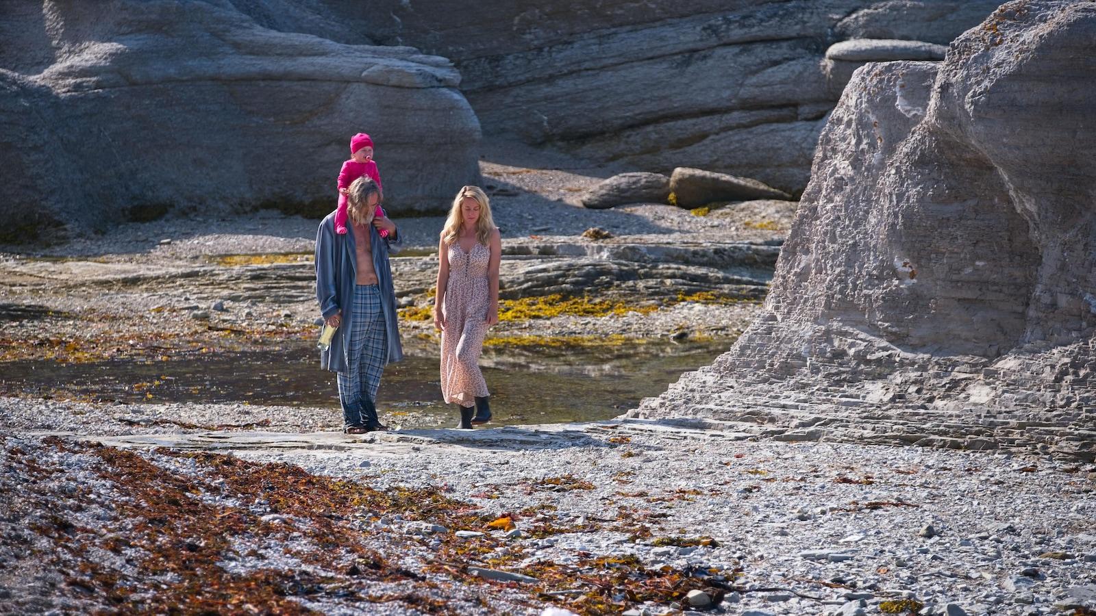 Sur une plage rocailleuse, un homme (Roy Dupuis) avec un bébé sur les épaules et une femme en robe claire (Christine Beaulieu) marchent.