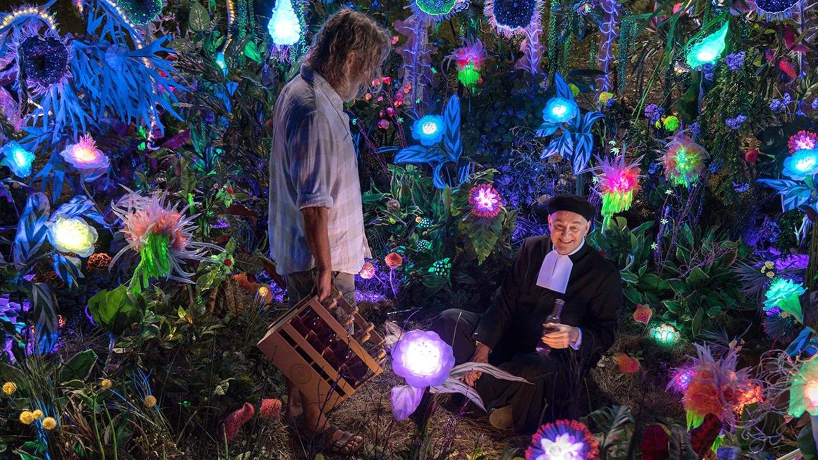 Au milieu de fleurs fluorescentes, la nuit, un homme debout (Roy Dupuis) regarde un autre assis et en soutane (Yves Jacques)