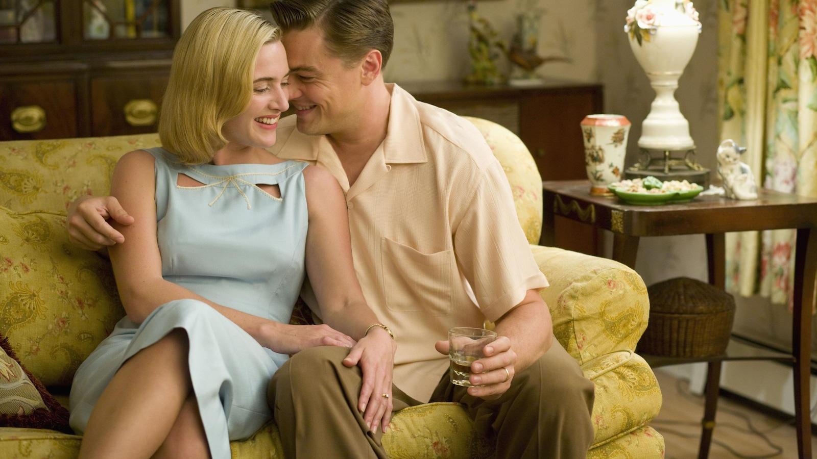 Un couple riant, assis collés sur un canapé jaune.