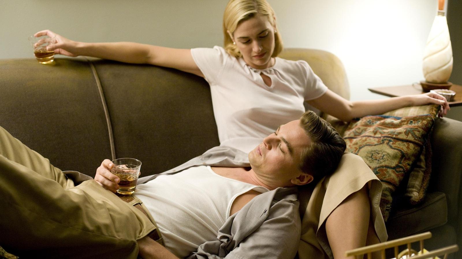 Une femme assise sur un canapé, un homme allongé la tête sur ses genoux, un verre d'alcool dans les mains.