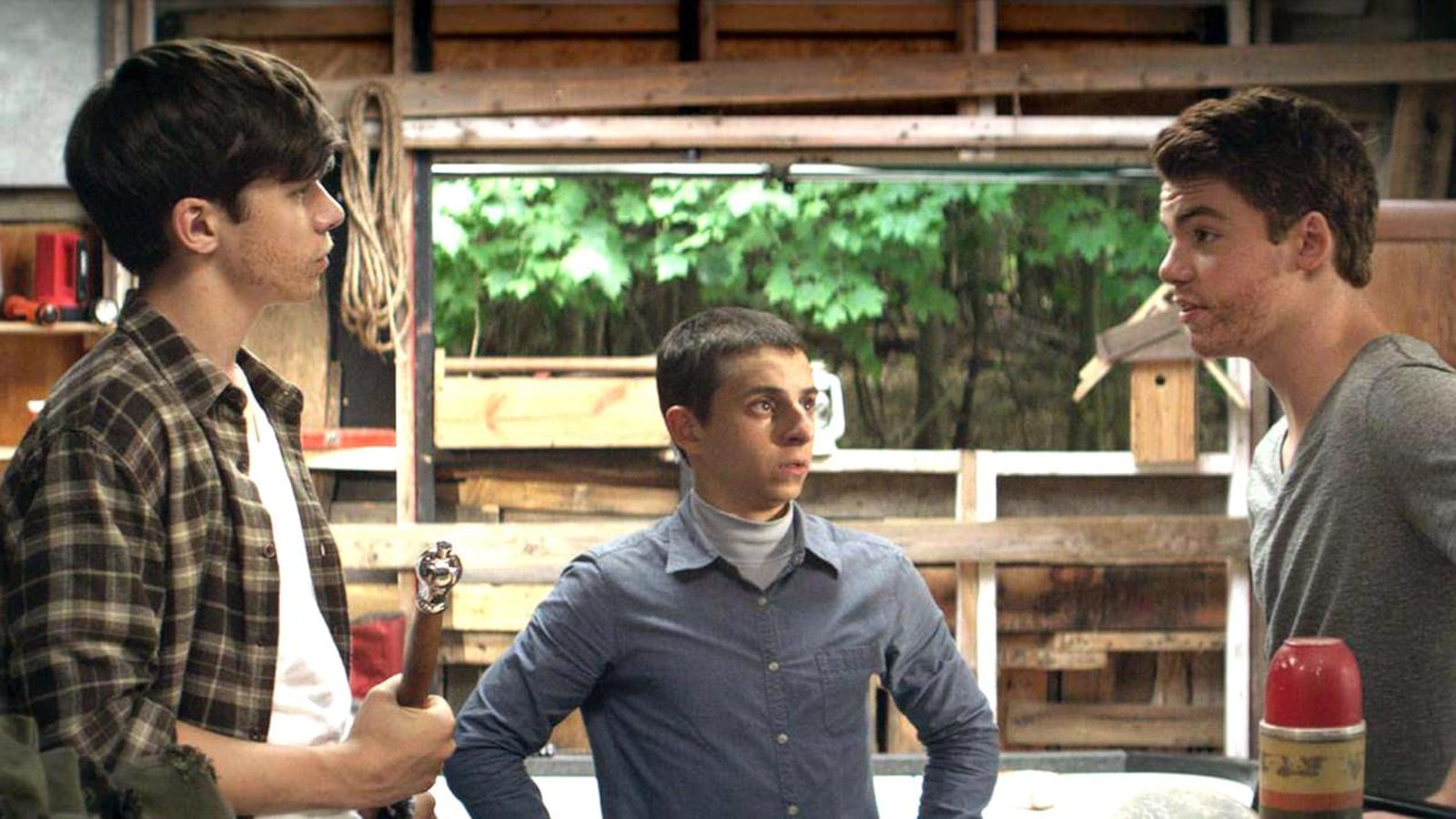 Trois jeunes garçons dans une cabane dans les bois.