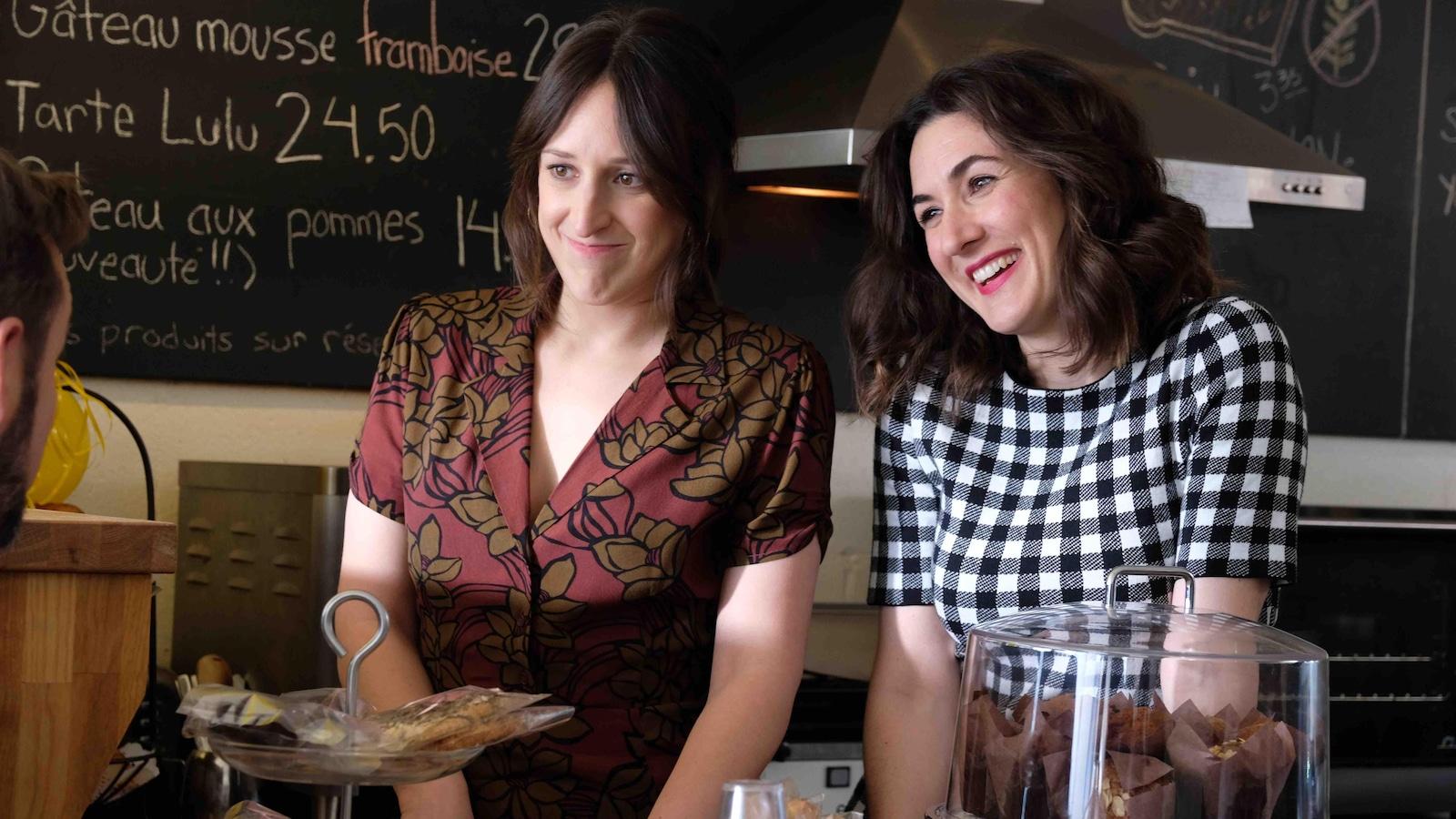 Maxim et Elizabeth sont derrière le comptoir d'un café qui contient des pâtisseries.