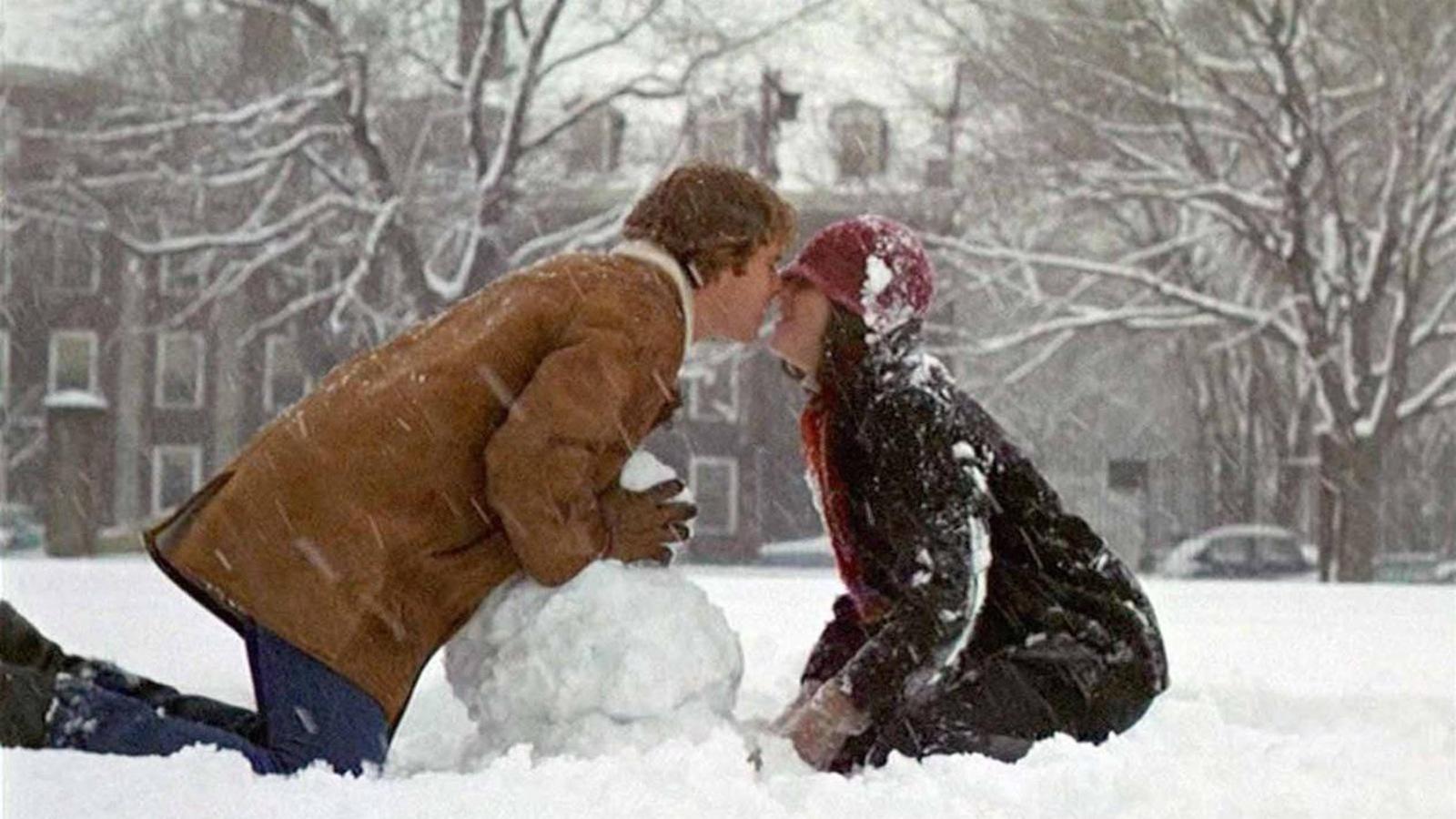 Un couple s'embrasse, sous la neige, au-dessus d'un bonhomme de neige qu'ils construisent.