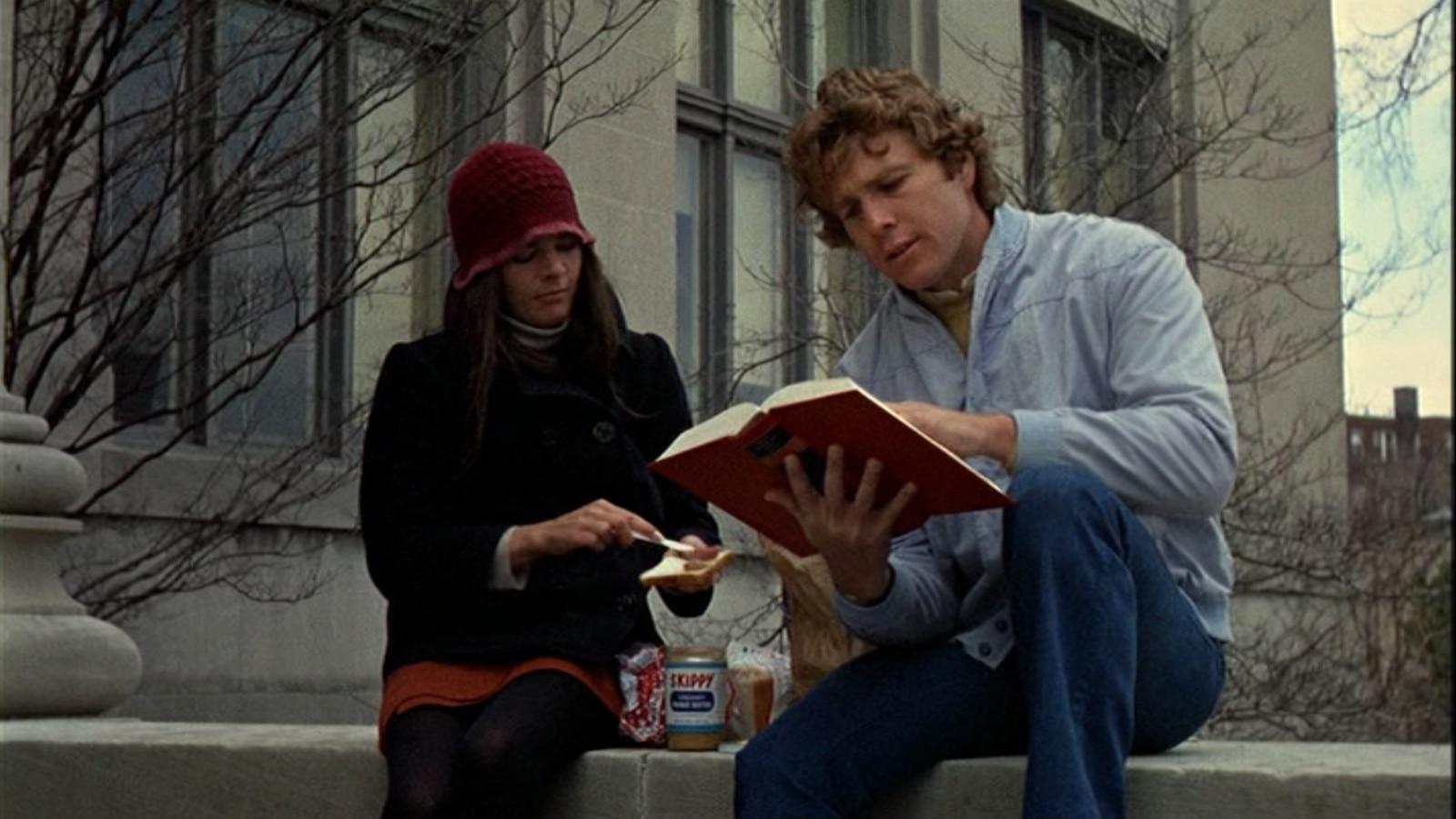 Assis sur un muret, une jeune femme tartine une toast et un jeune homme lit un livre.