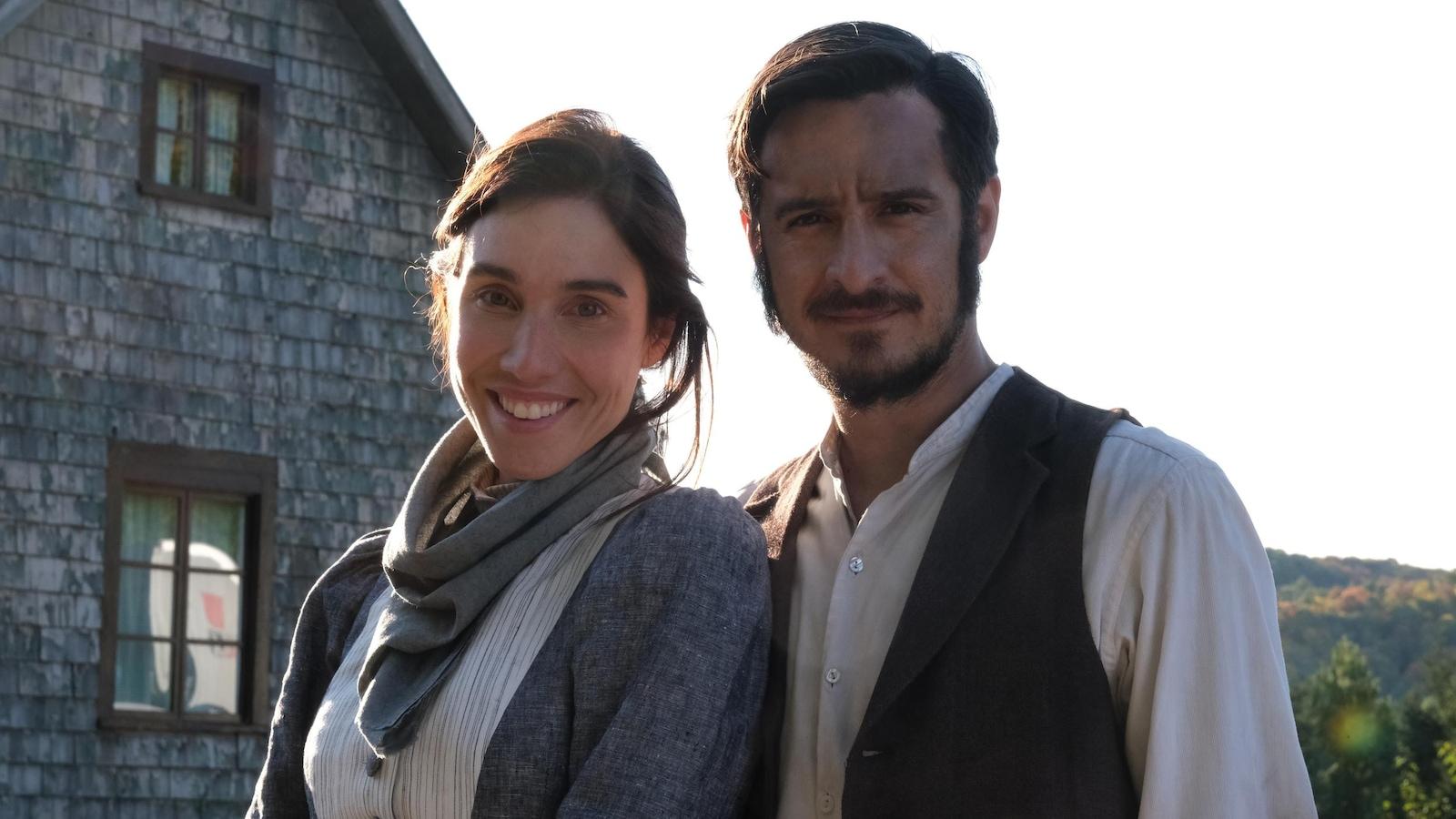 Le duo est dans un décor d'antan, en campagne.
