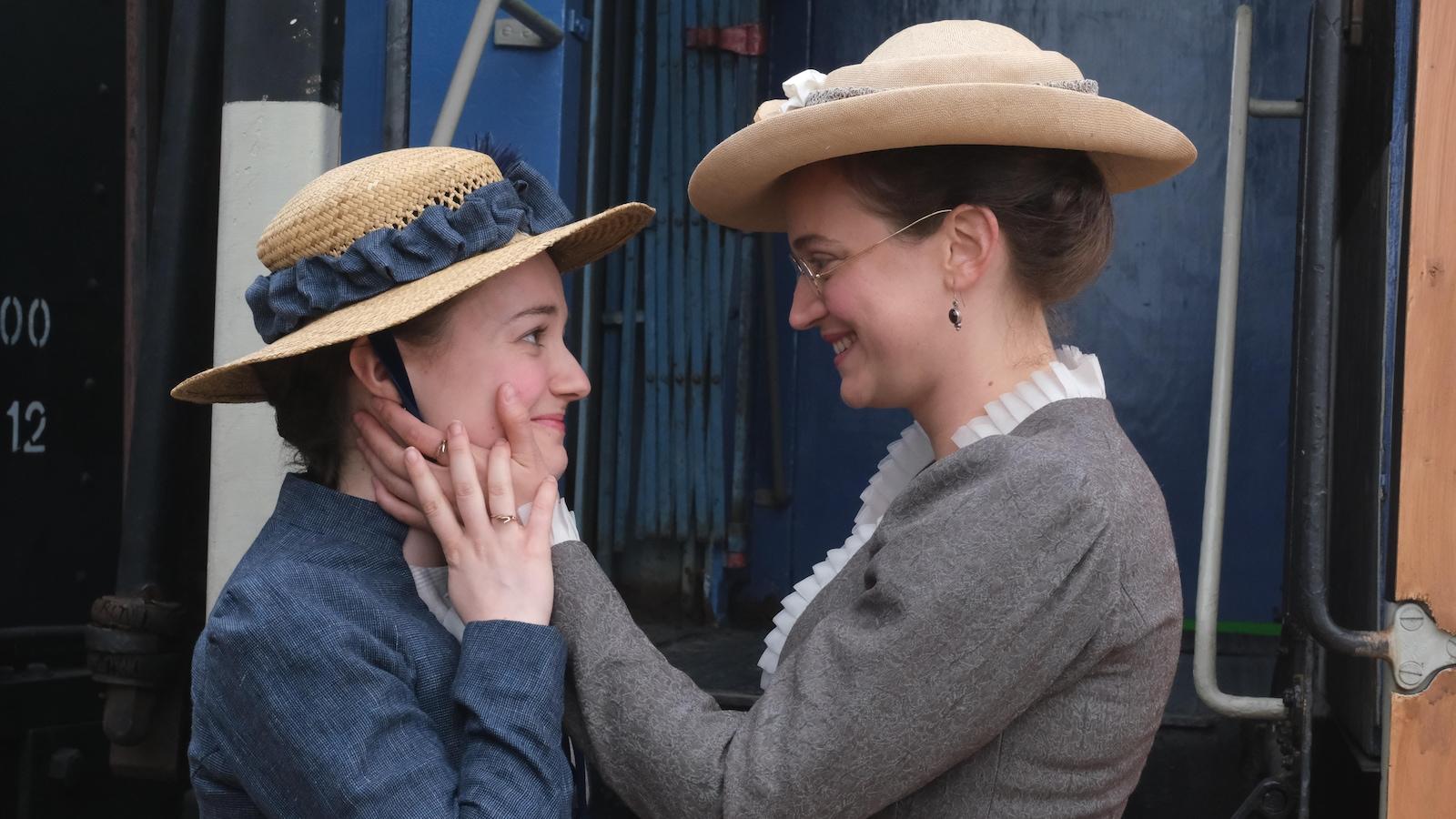 Deux femmes se regardent amoureusement devant un train dans des costumes d'époque.