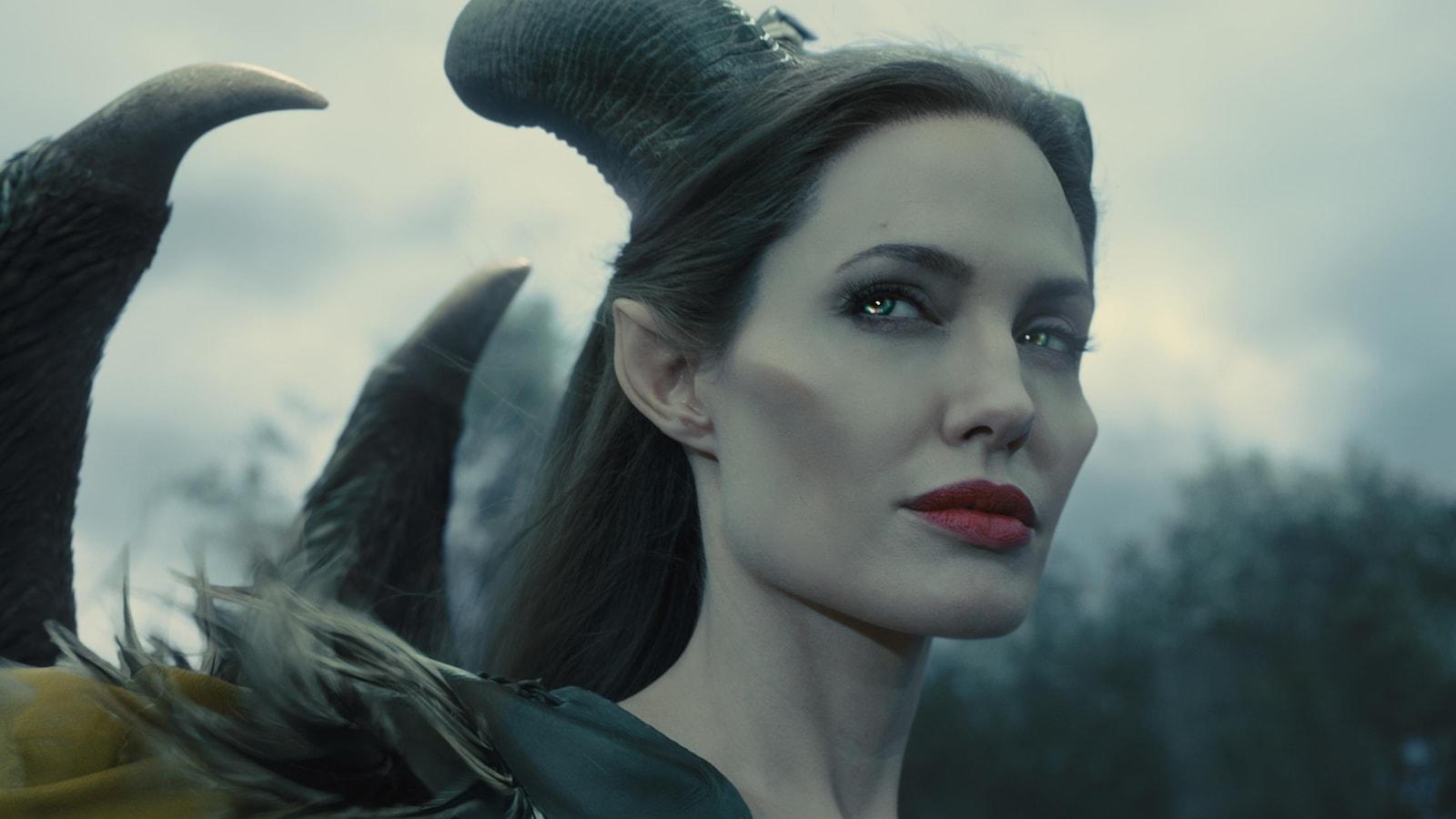 Une femme au visage anguleux, des cornes sur la tête et dans le dos.