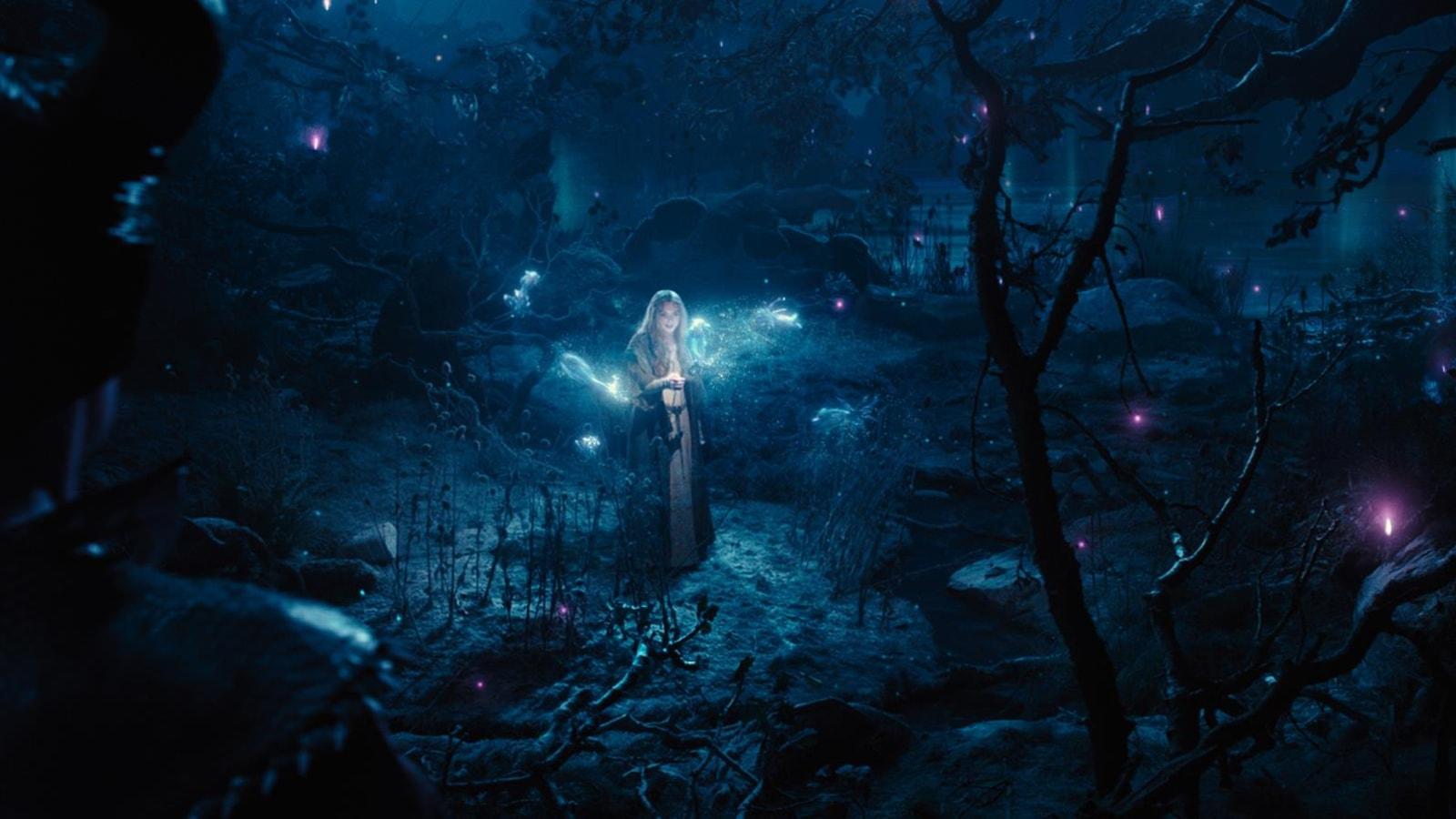 Une fille au milieu d'une clairière en pleine nuit, entourée de feux follets violets.