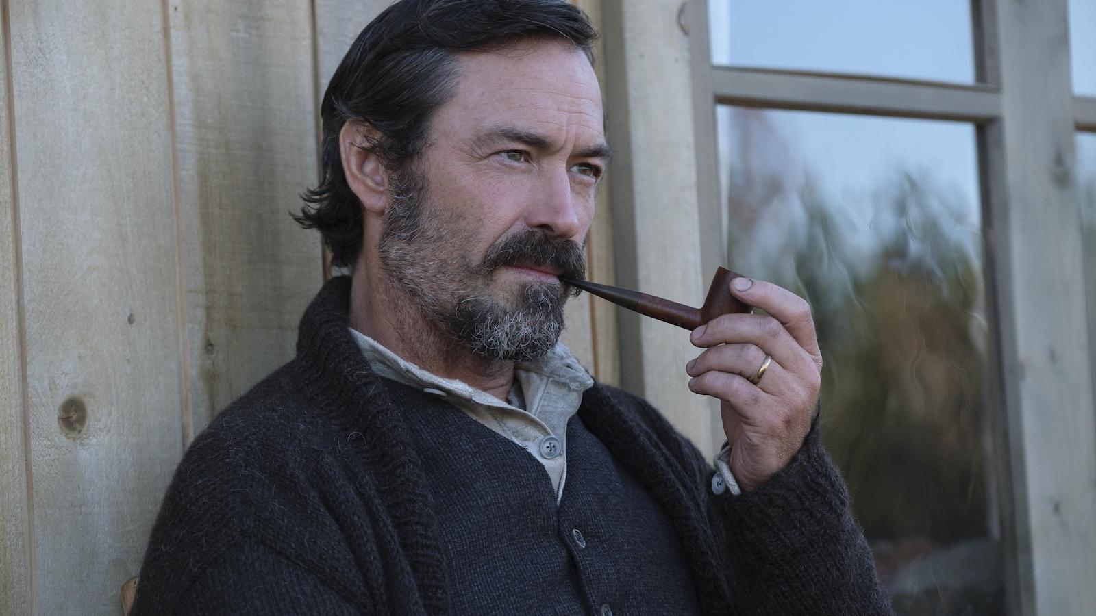 Un homme (Sébastien Ricard), l'air pensif, fume la pipe, devant une maison.
