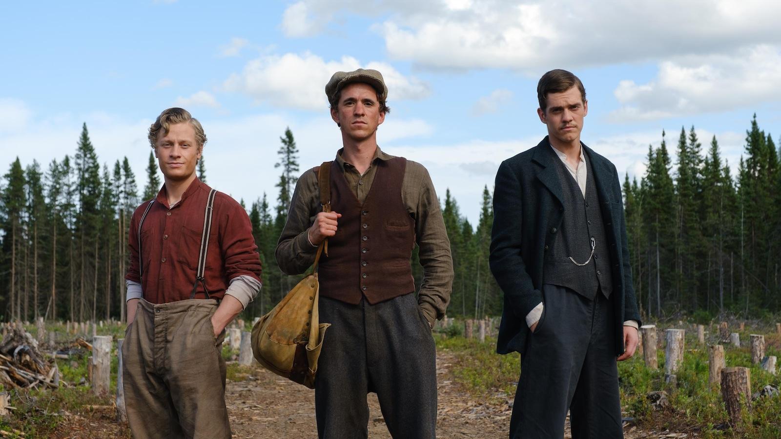 Trois jeunes hommes (Antoine-Olivier Pilon, Emile Schneider et Robert Naylor), debout, devant une terre forestière.