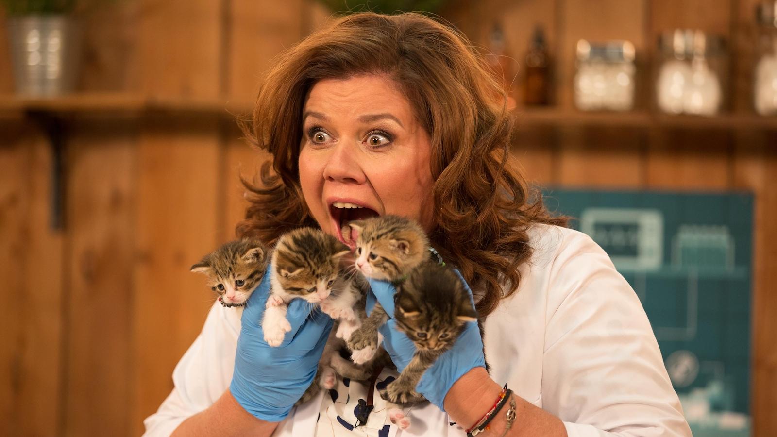 Elle tient quatre bébés chats dans ses mains, devant son visage et semble très excitée.