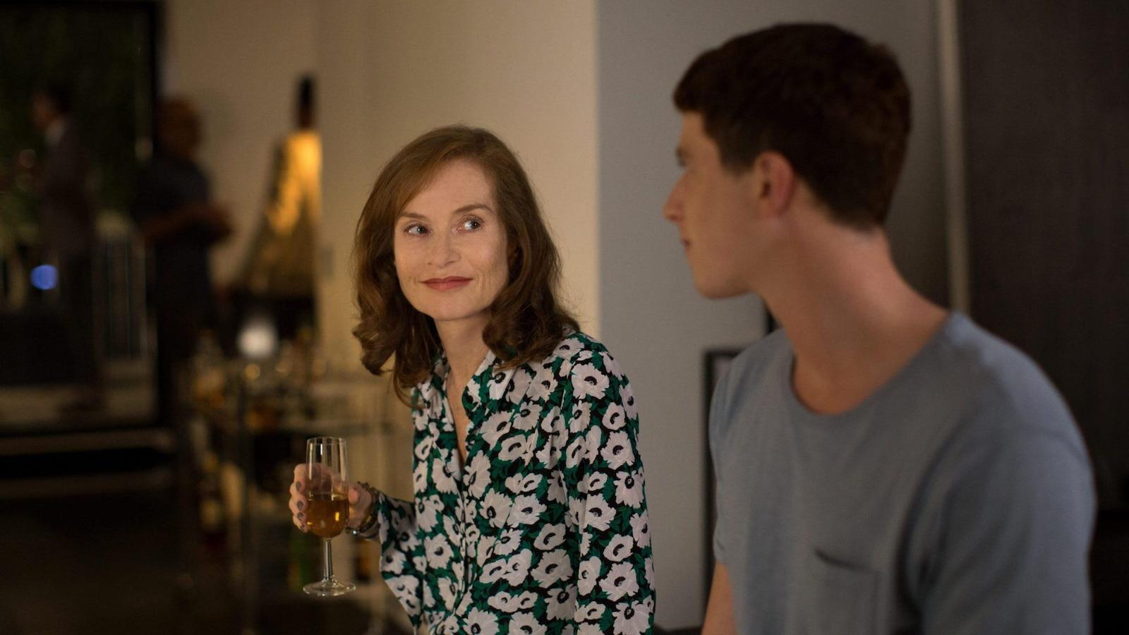 Une femme (Isabelle Huppert) tenant une coupe de champagne regarde tendrement un jeune homme.