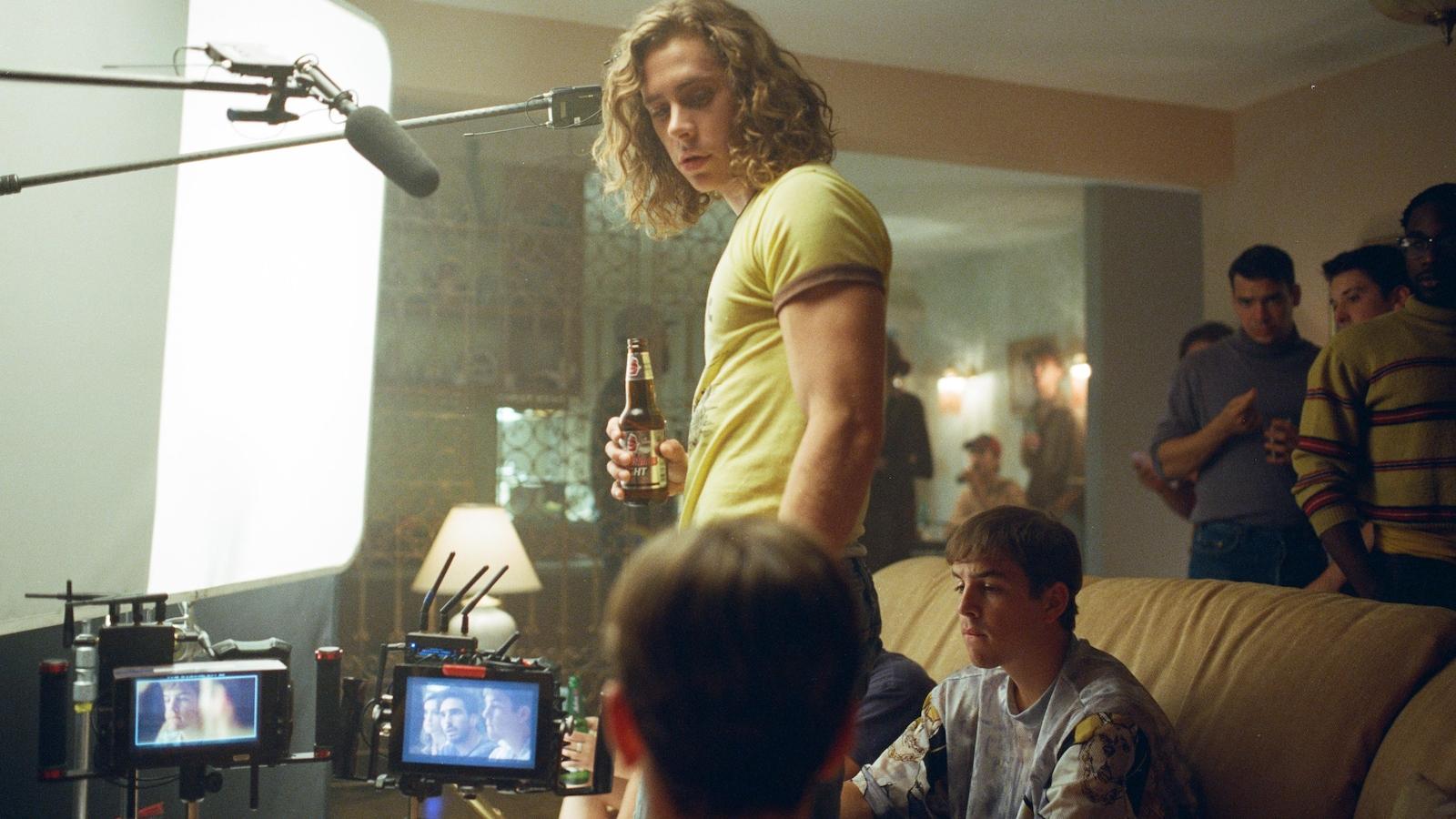 Sur un plateau de tournage, un jeune homme debout devant d'autres jeunes hommes assis sur un canapé.