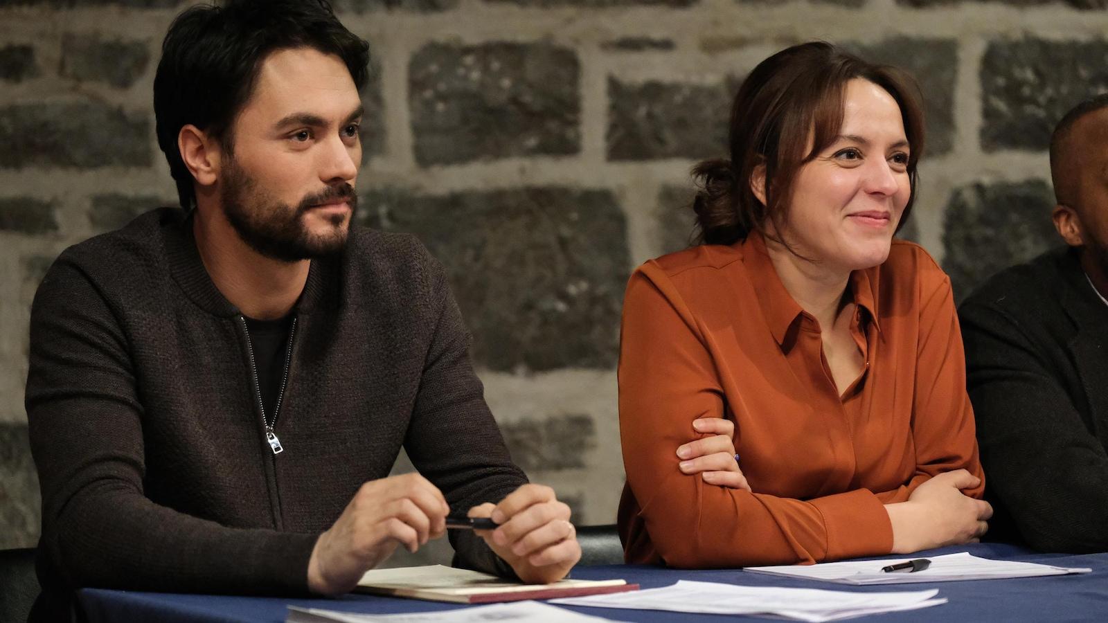 Les deux personnes sont assises à une table et sourient.