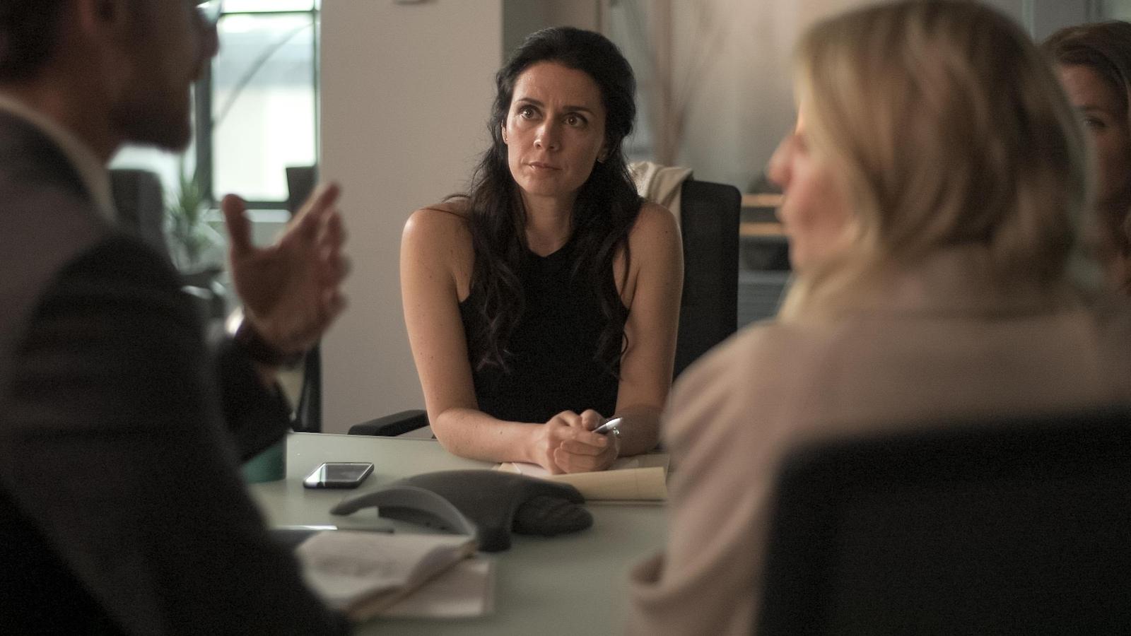 Elle écoute attentivement ce que dit son collège. Elle est assise dans une salle de réunion.