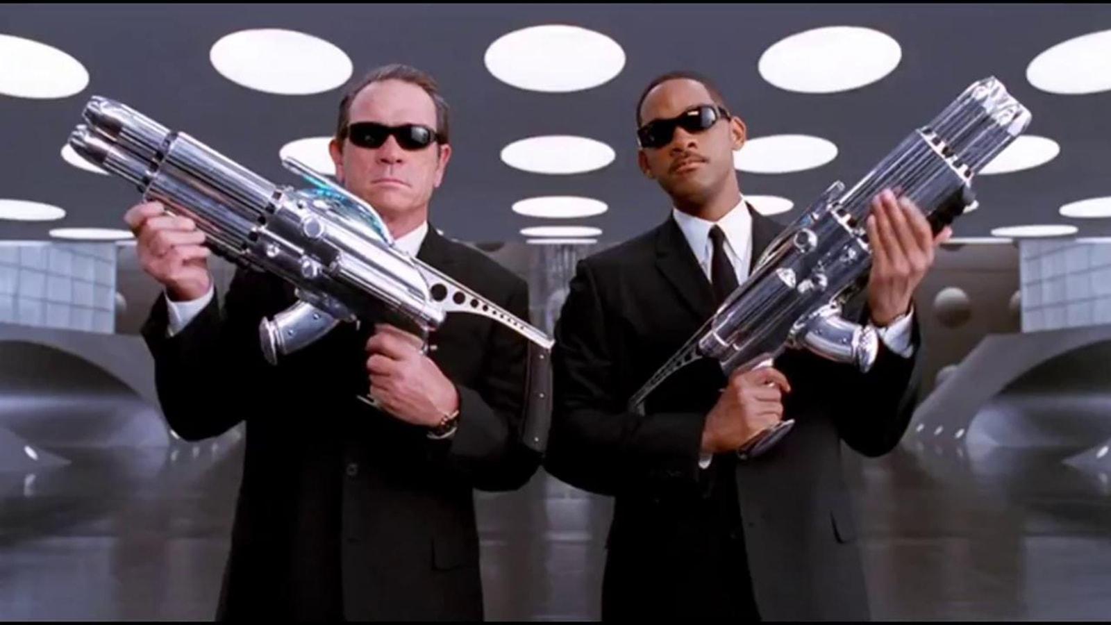 Deux hommes en costumes et lunettes noires tiennent d'énormes armes dans leurs bras