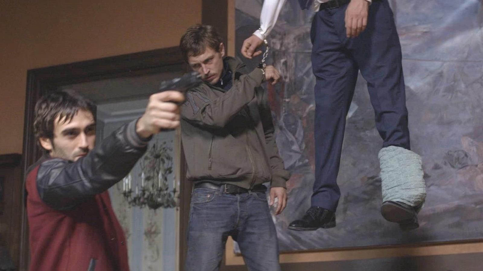 Un jeune homme tient un pistolet, un autre derrière lui est menotté à un pendu