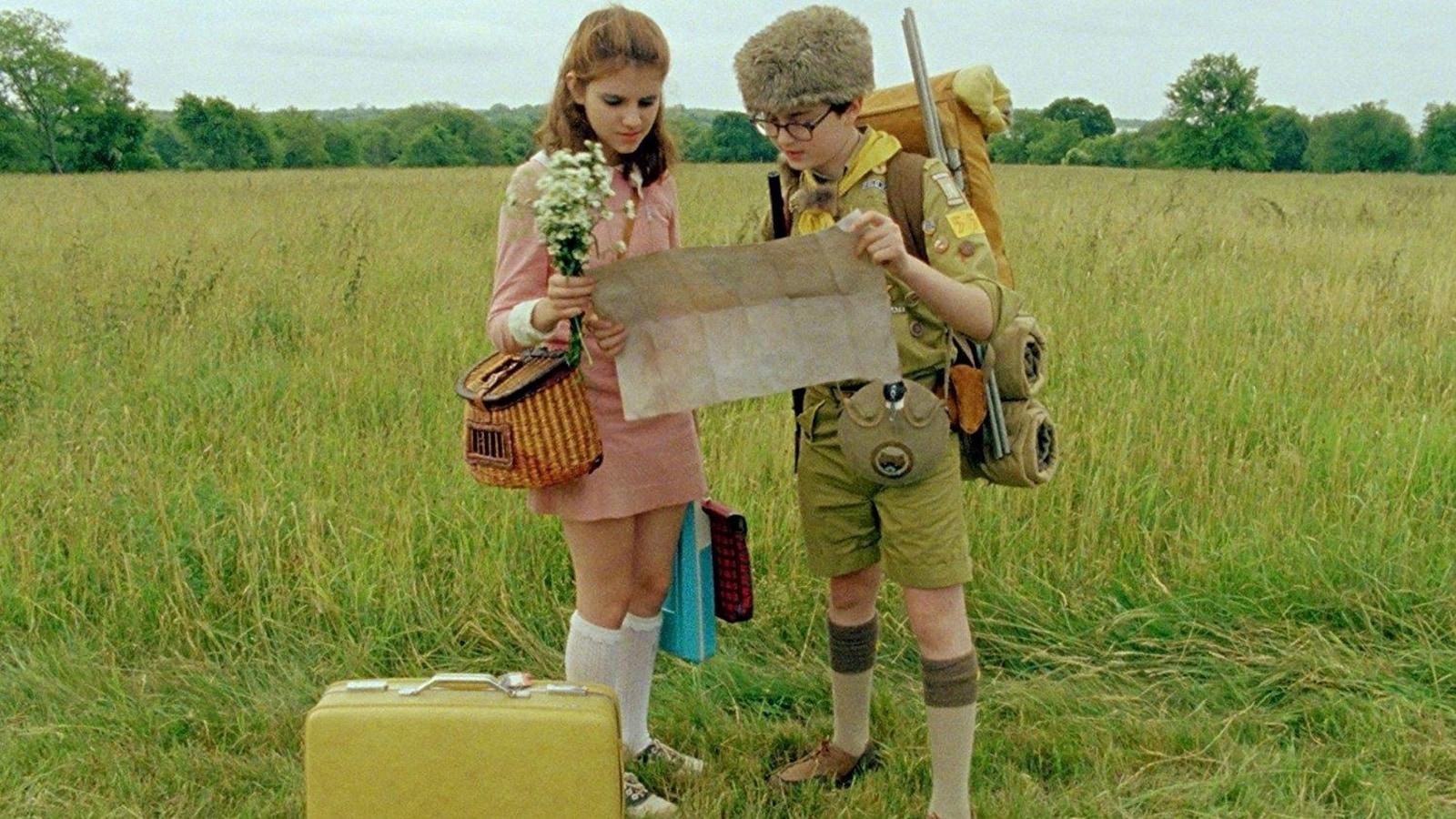 Une petite fille et un petit garçon habillé en scout regardent une carte dans une prairie.