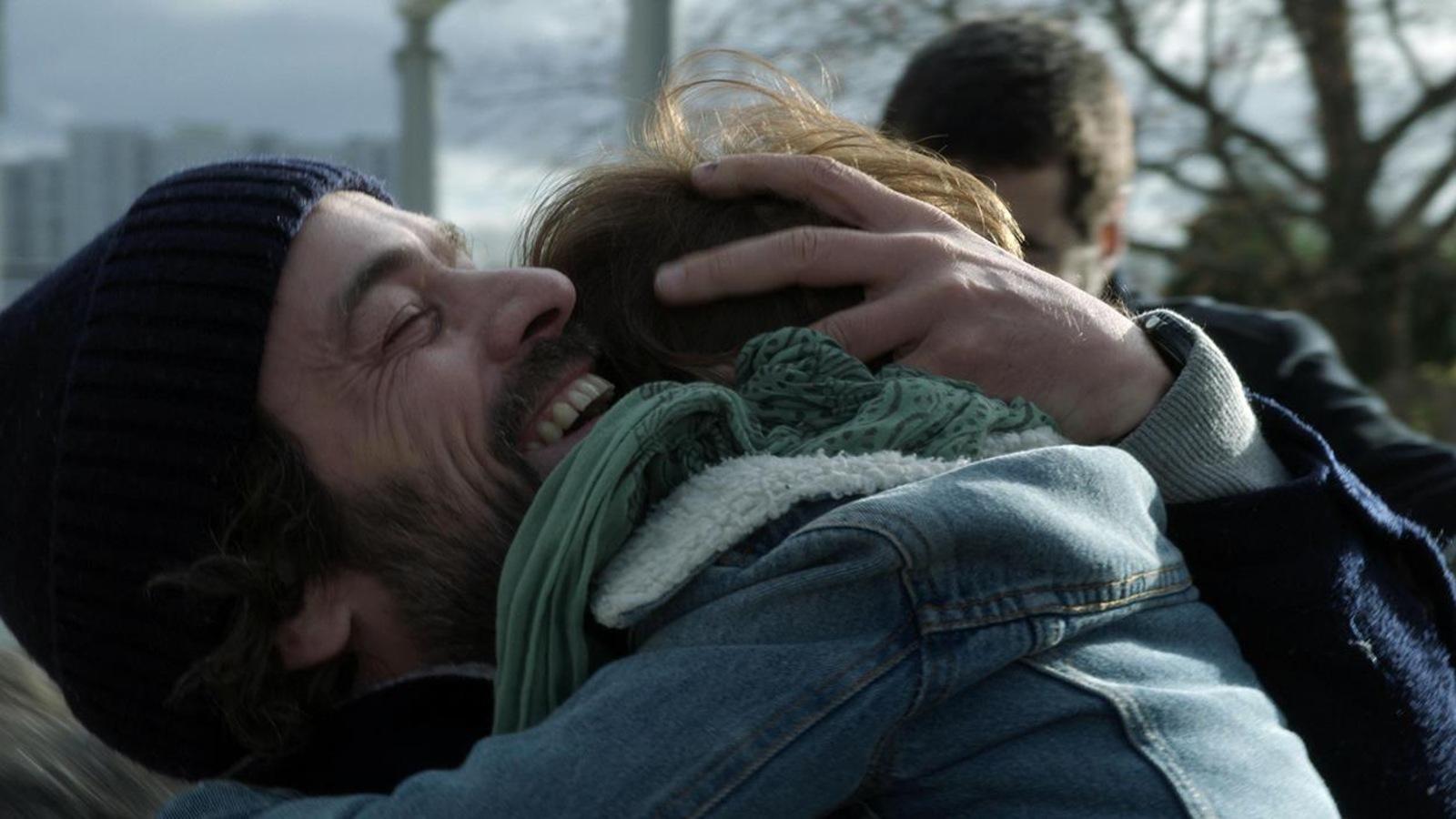 Un homme tient un enfant dans ses bras et contre lui, en souriant.