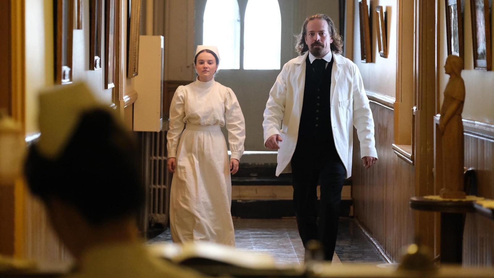 Le duo marche dans un corridor habillé en infirmière et en médecin d'époque.