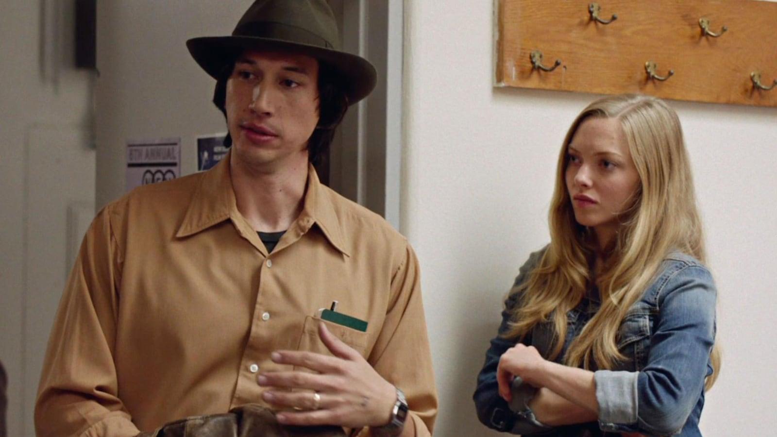 Un homme avec un chapeau (Adam Driver) et une femme (Amanda Seyfried), dans un couloir.