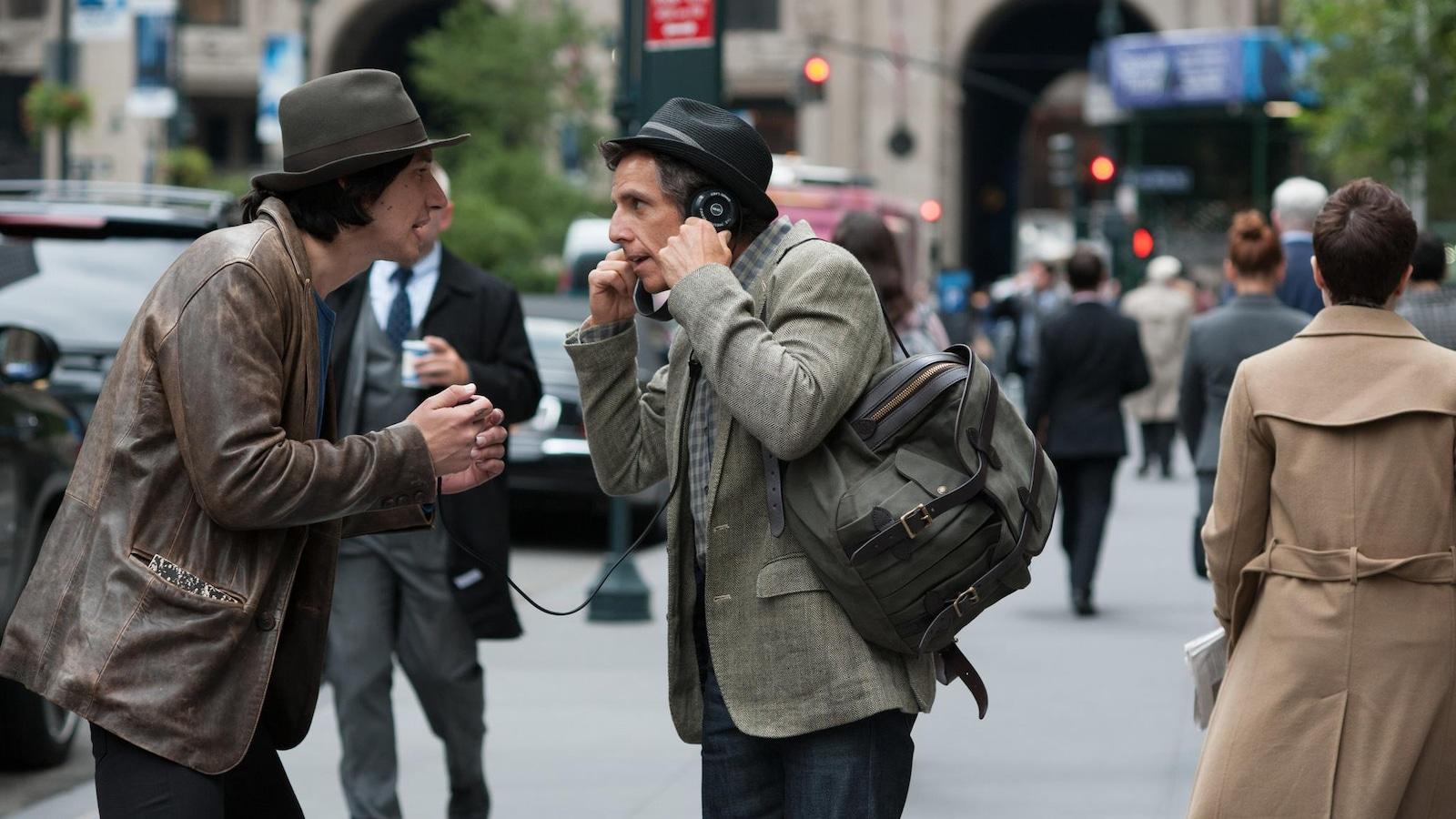 Dans la rue, un homme portant un chapeau (Adam Driver) fait écouter avec des écouteurs quelque chose à un autre homme portant aussi un chapeau (Ben Stiller).