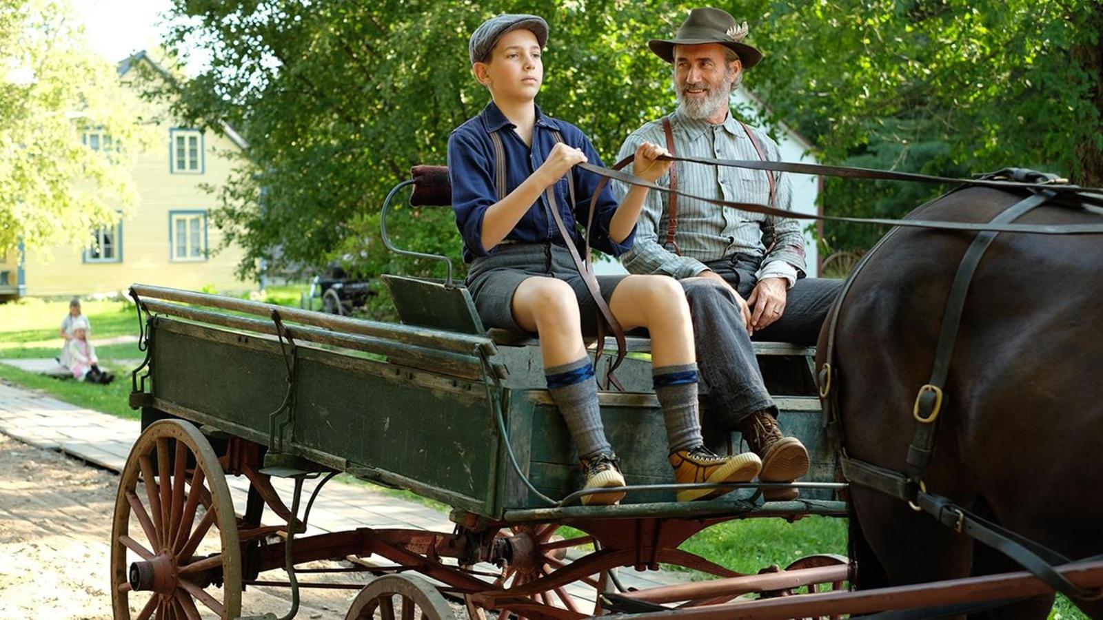 Un père et son fils conduisent une carriole