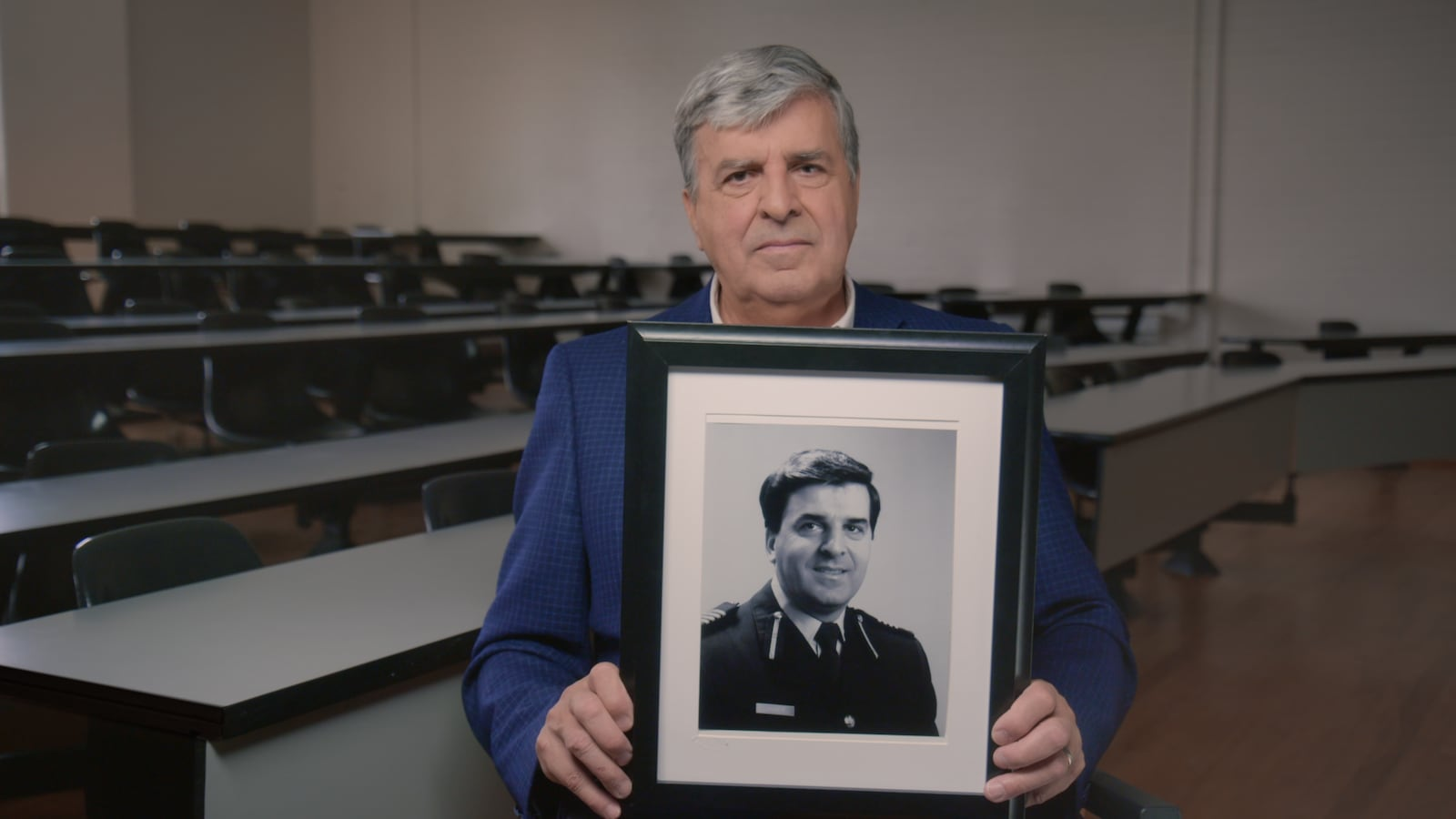 L'homme tient une photo de lui 30 ans plus tôt.