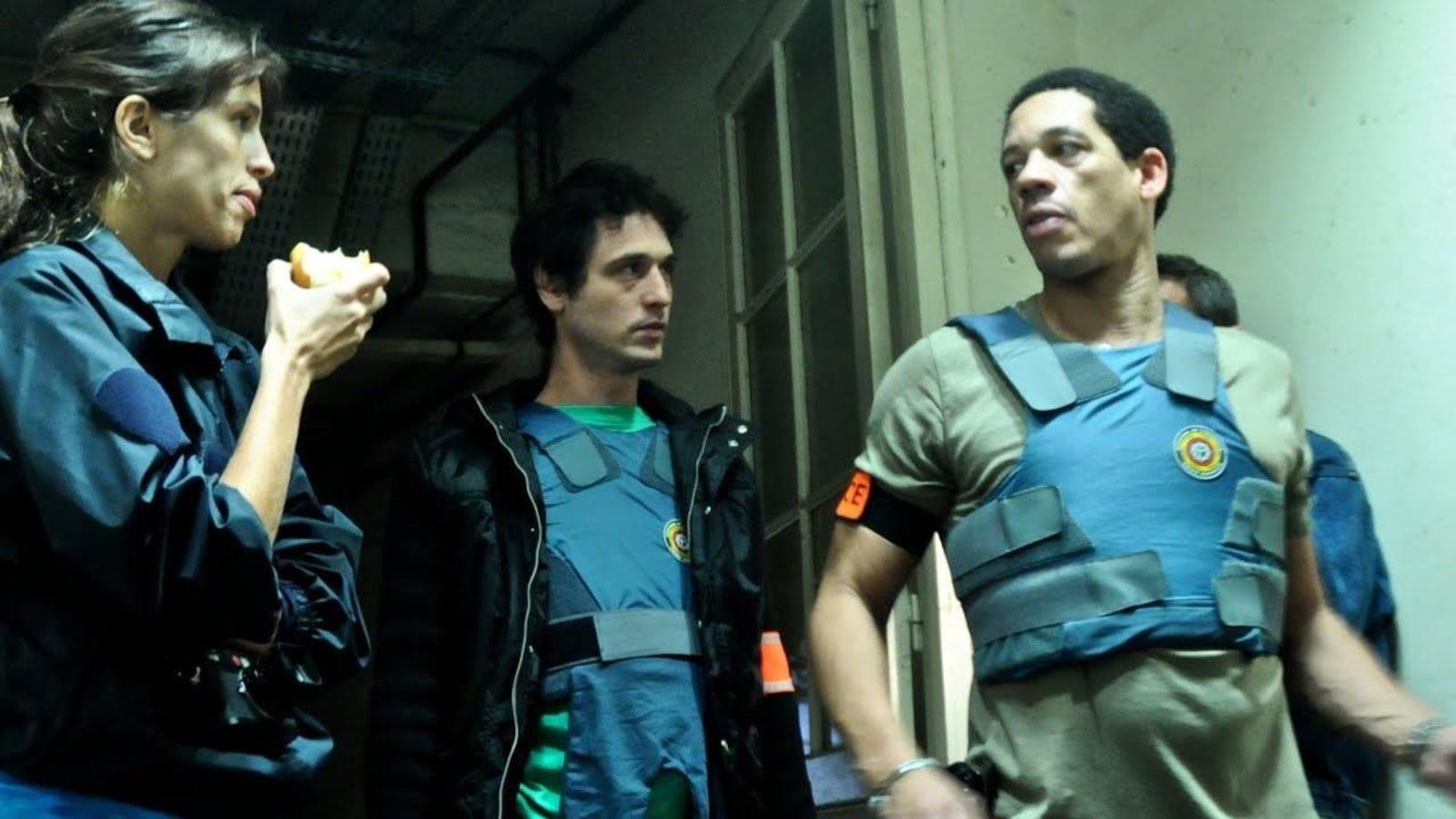 Des policiers avec des gilets pare-balles debout dans un couloir.