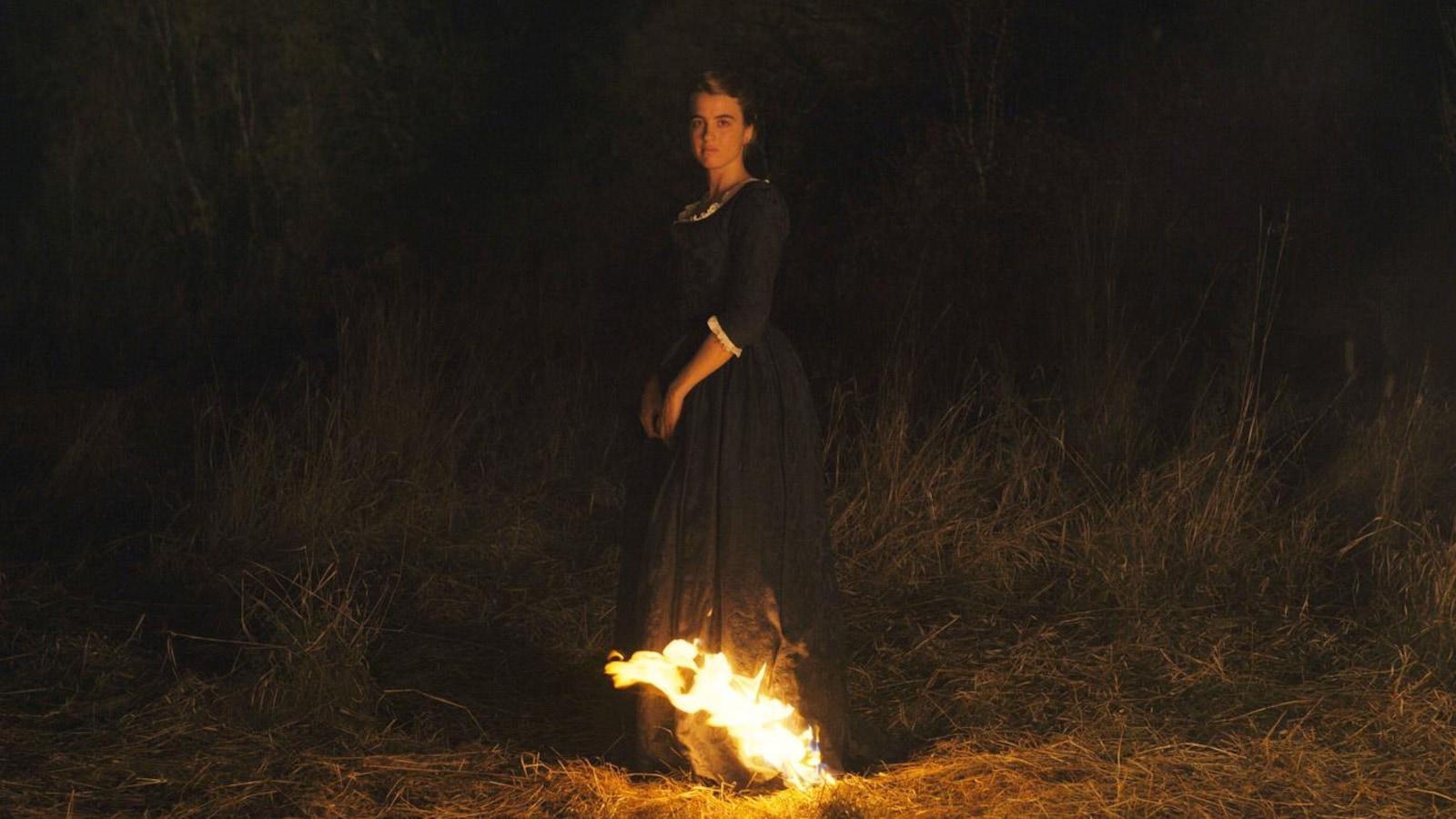 Une jeune femme en robe d'époque devant un feu dans un champ, la nuit.