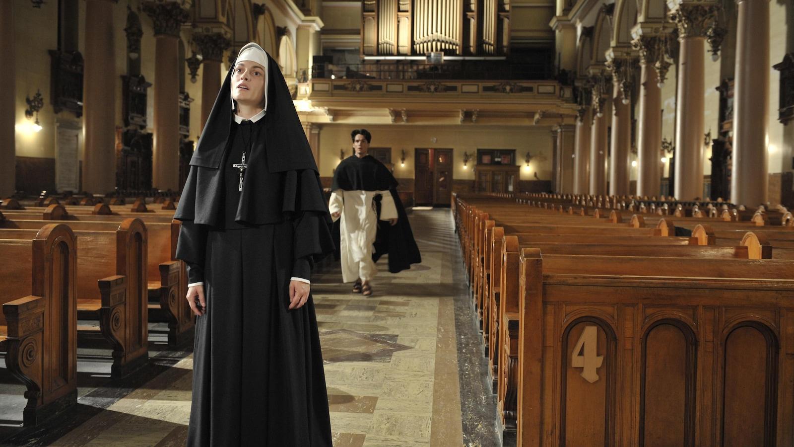 Une soeur en tenue, au milieu d'une église. Un prêtre arrive derrière elle.