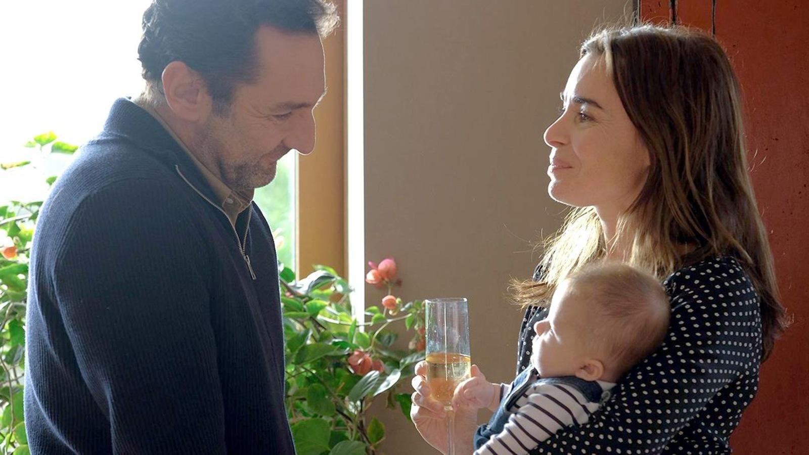 Un homme regarde une femme qui tient un bébé dans ses bras.